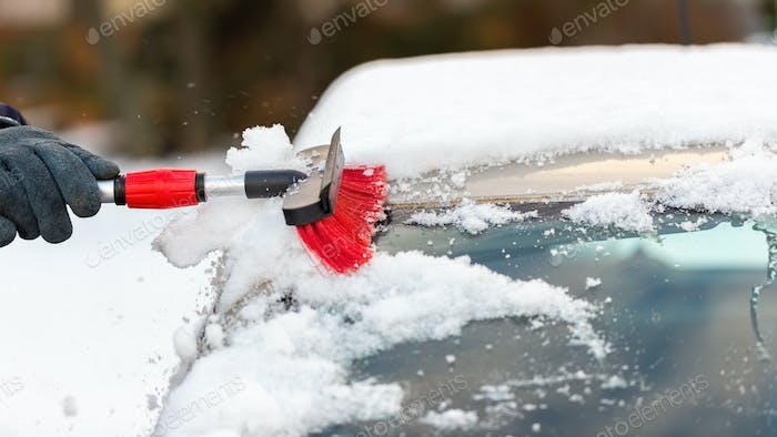 Human hand cleaning car from snow in wintertime day