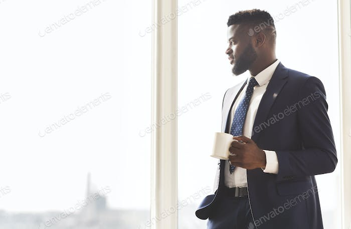 Young successful businessman drinking coffee in office