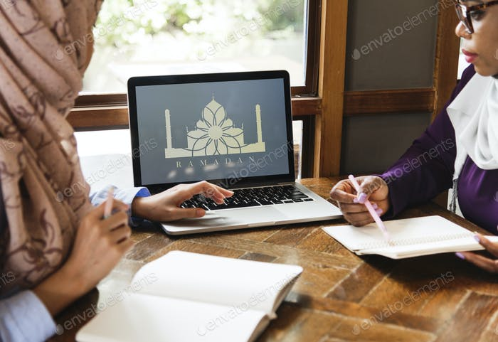 Islamic women discussing and using laptop for working