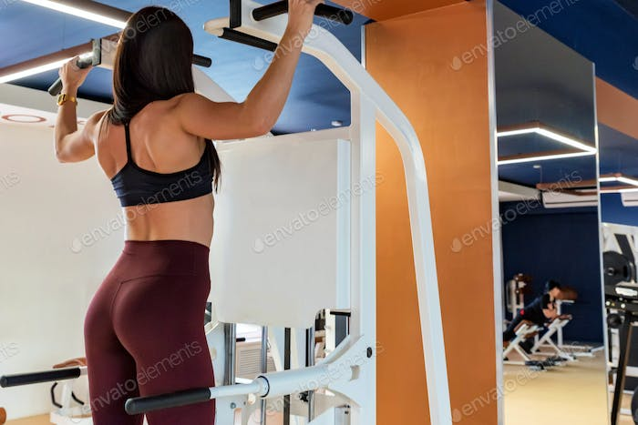 Back view female athlete does back exercises in gym