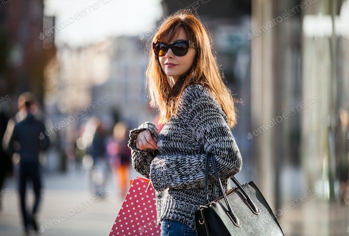Urban scene, Woman walks on street with shopping bags