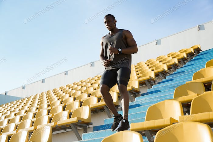 Young african man runner in sport clothes running downstairs a