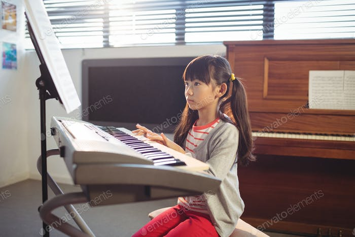 Concentrated girl looking at notes while practicing piano
