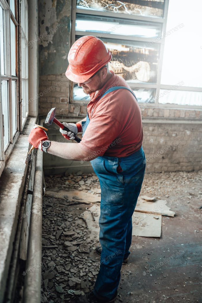 Strong highly skilled worker handling a windowsill on a large construction site