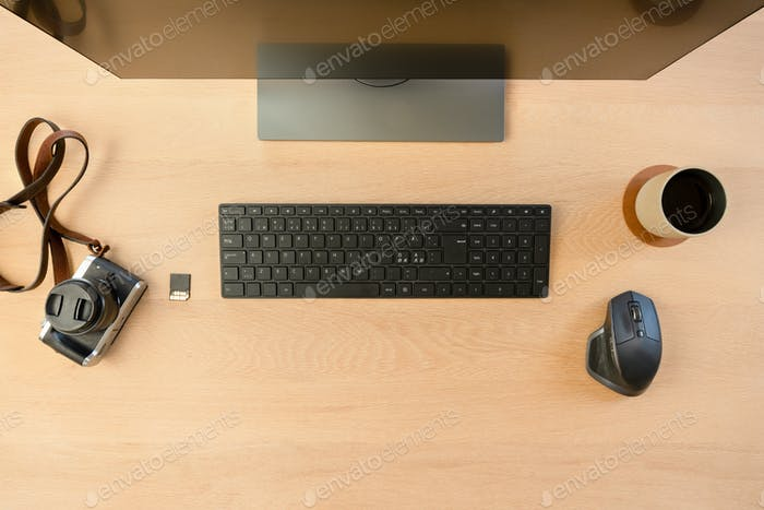 Top View of Creative Office Desk with Monitor and Camera with Hot Cup of Coffee