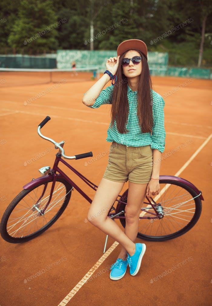 Girl hipster standing with magenta bike on the tennis court