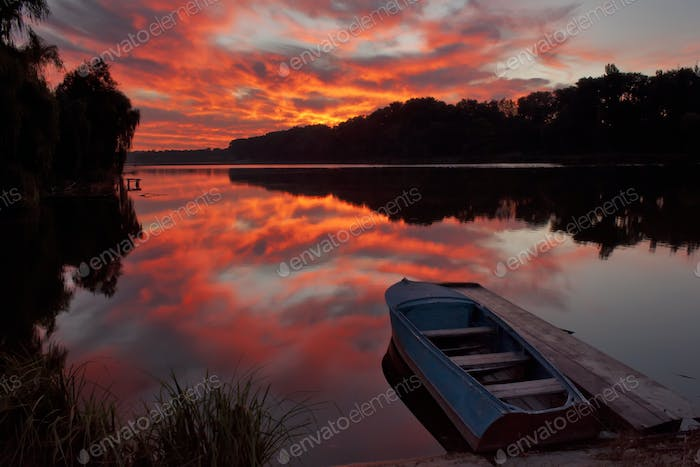Beautiful dawn at the lake with a boat