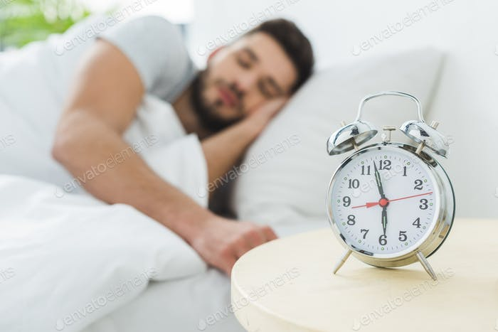 alarm clock on table, man sleeping in bed on background