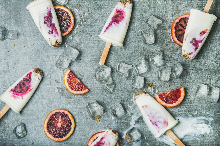 Blood orange, yogurt and granola popsicles on ice, grey background