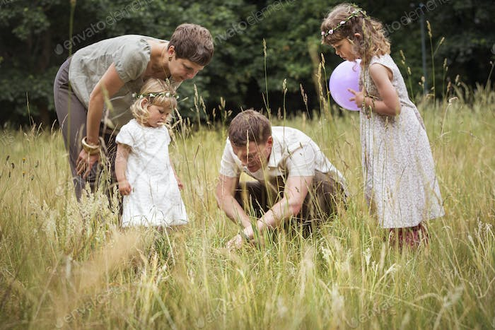 Family with two children playing in a meadow.