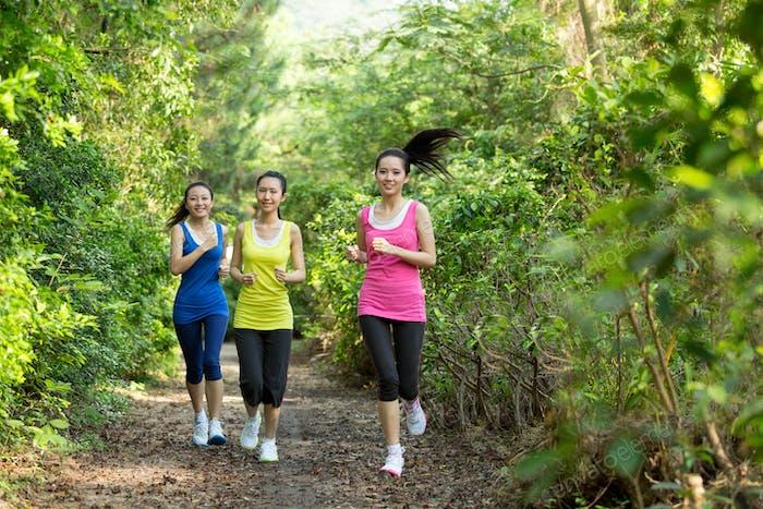Drei Freundinnen laufen zusammen auf dem Weg