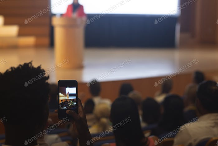 Man with smartphone taking video of businesswoman in the auditorium