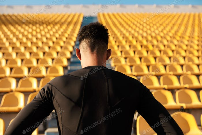 Back view of young strong African American sportsman among empty stadium seats