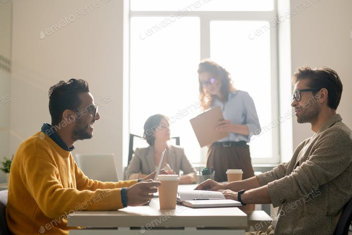 Positive young multi-ethnic marketing experts sitting at table