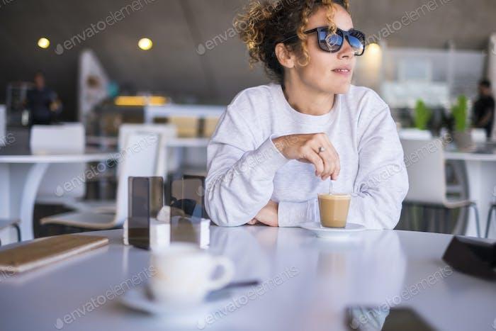 красивые кавказские женщины среднего возраста с солнцезащитными очками берут и пьют кофе в баре