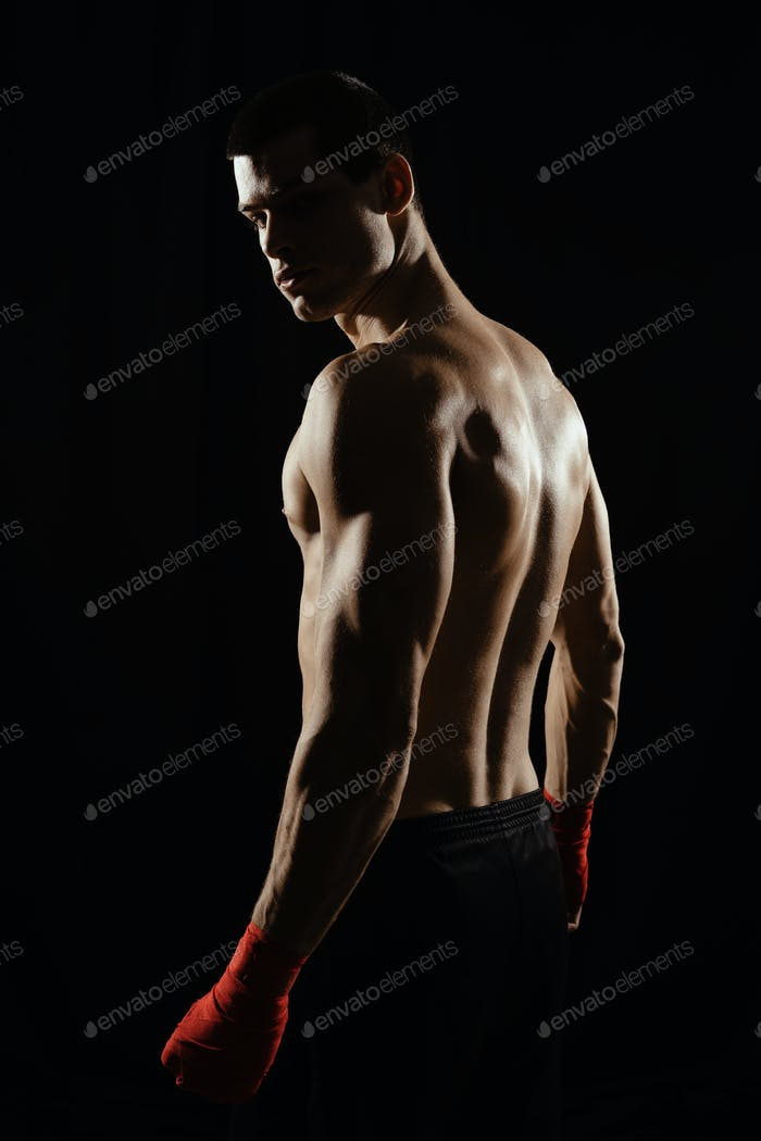 Portrait of male boxer looking over shoulder