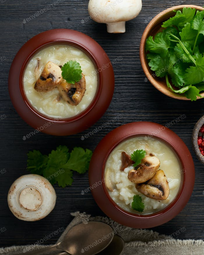 Unconventional unusual serving of risotto with mushrooms in pot. Rice porridge with mushrooms.