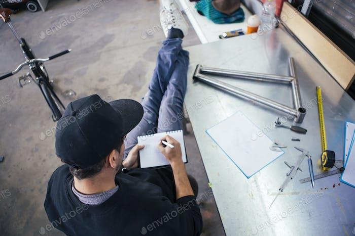 Man in cap writing measurements in notebook