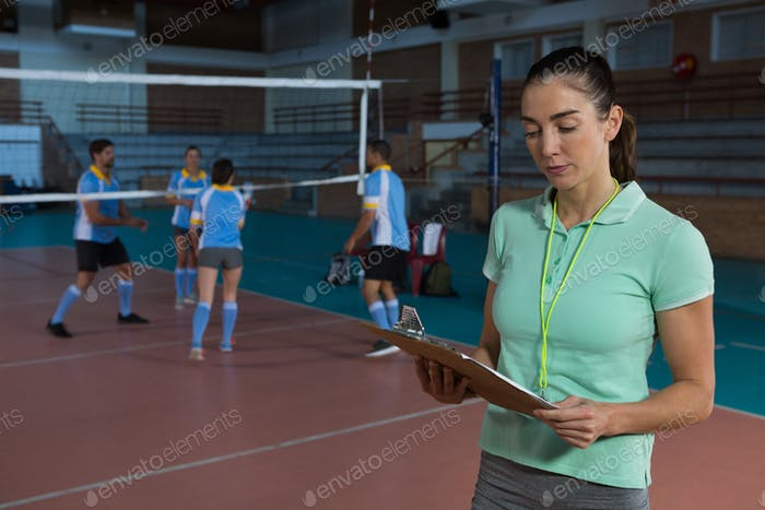 Coach holding clipboard at volleyball court