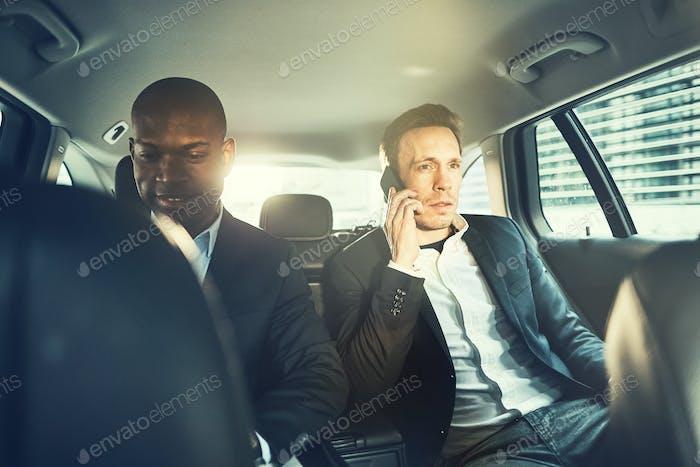 Два бизнесмена, работающие на заднем сиденье автомобиля