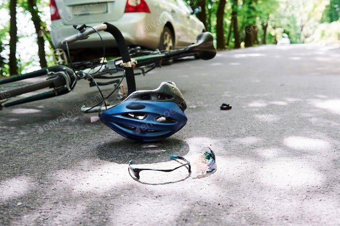 Conception of carelessness. Bicycle and silver colored car accident on the road at forest at daytime