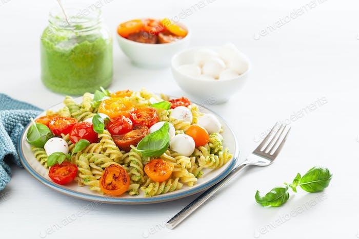 healthy fusilli pasta with pesto sauce, roasted tomatoes, mozzar