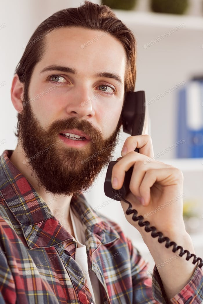 Hipster businessman making a call in his office