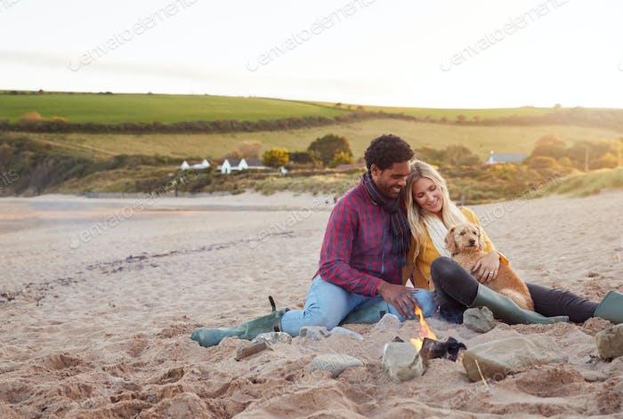 Liebevolles Paar mit Hund Entspannend durch Feuer Auf Winter Strand Urlaub