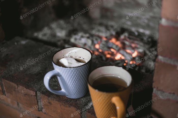Focused two cups against the background of a fireplace