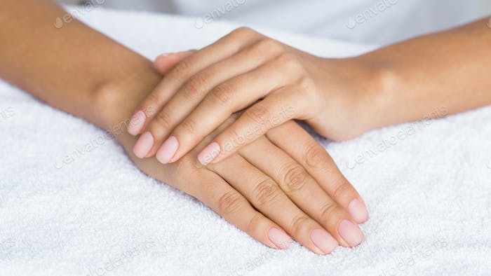 Nude manicure. Female hands on white towel