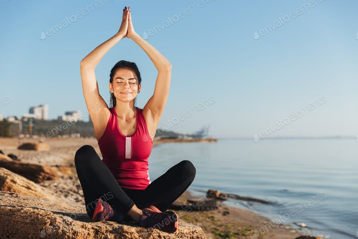 Satisfied young sportswoman sitting in yoga position