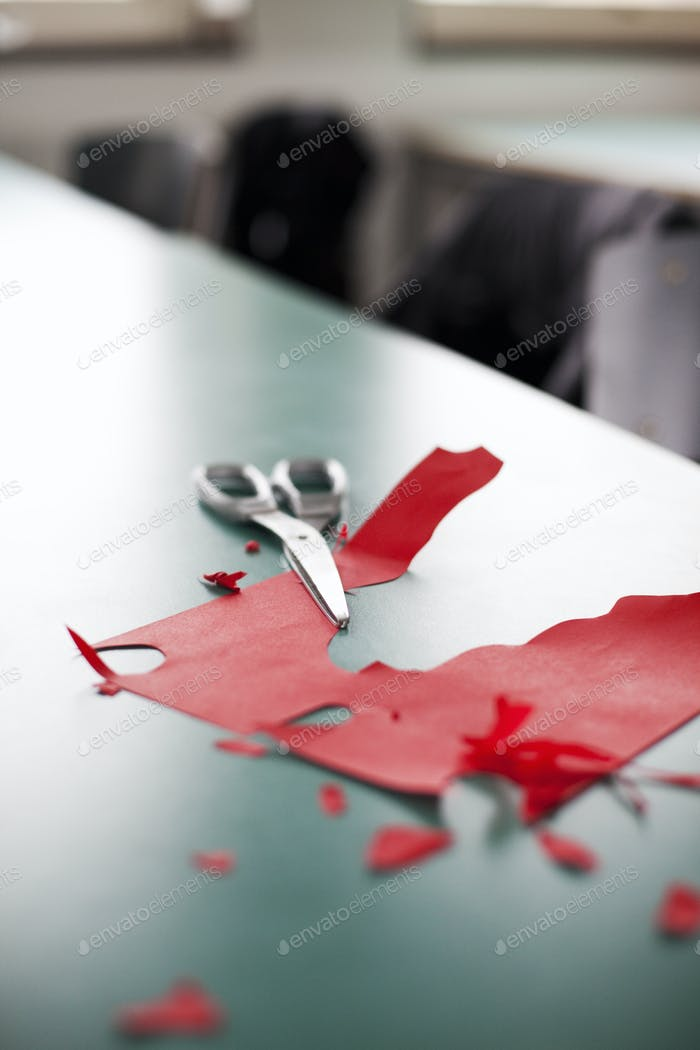 Close-up of scissors and red craft paper on table