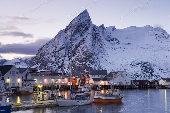 Fishing boats moored in harbour of settlement, with snow-capped mountains behind.