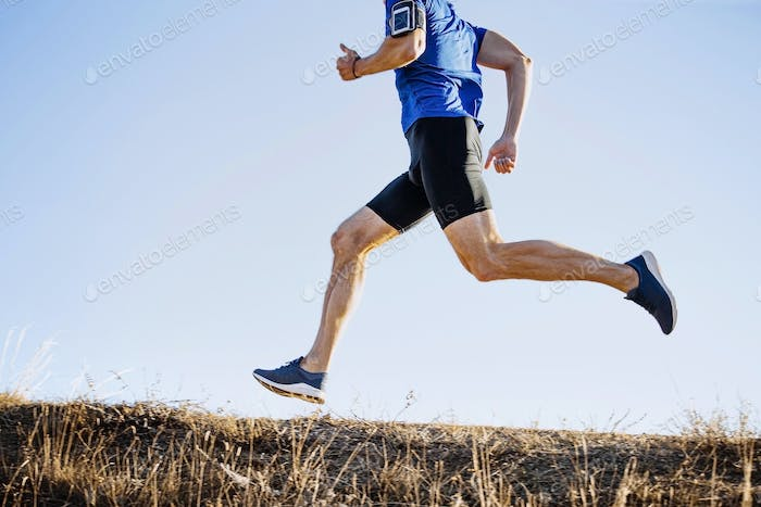 male runner running mountain trail