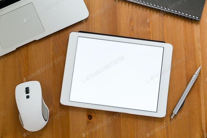 Moderner Schreibtisch mit Tablet mit einem leeren Bildschirm für Werbung