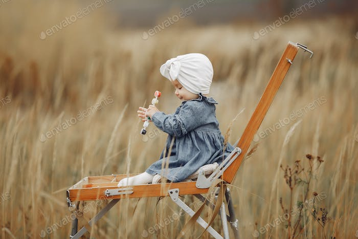Cute little girl painting in a autumn field