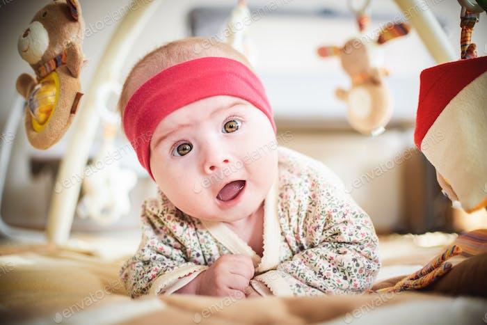 Cute surprised baby girl on floor looking up at camera