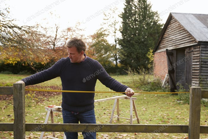 Mature Man Measuring Garden Fence For Repair