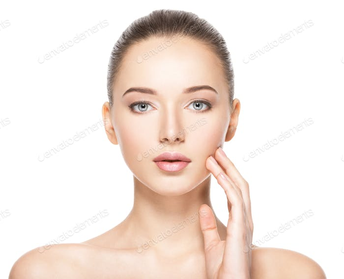 Young woman with healthy clean skin touches the face. Skin care concept.