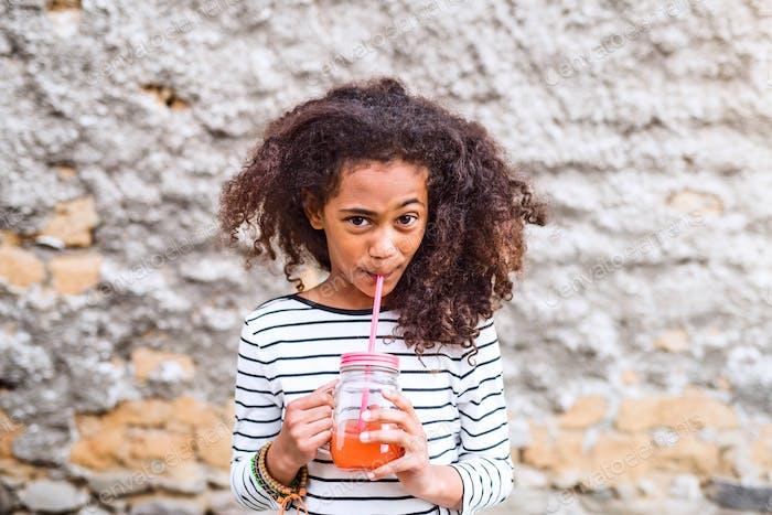 Schöne afrikanische amerikanische Mädchen trinken Saft, alte Beton wal