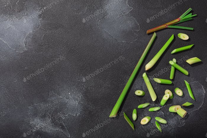Lemongrass, cut stems atop dark textured backdrop w/ copy space,  top view