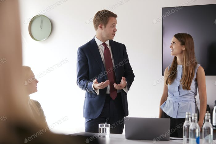 Businessman Addressing Group Meeting Around Table At Graduate Recruitment Assessment Day