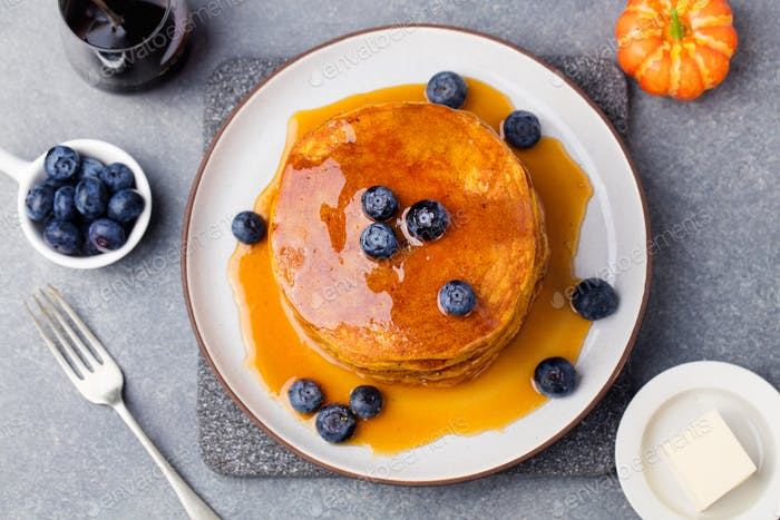 Pumpkin pancakes with maple syrup and blueberries on a plate Grey stone background Top view