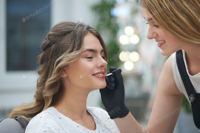 Makeup artist applying lip gloss in beauty salon