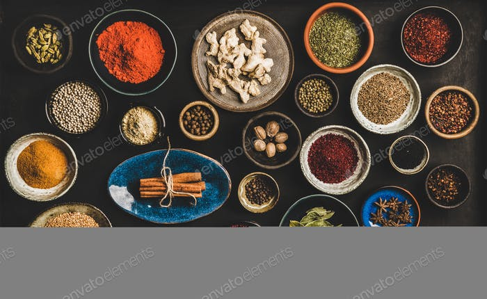 Flat-lay of different spices in bowls over dark background