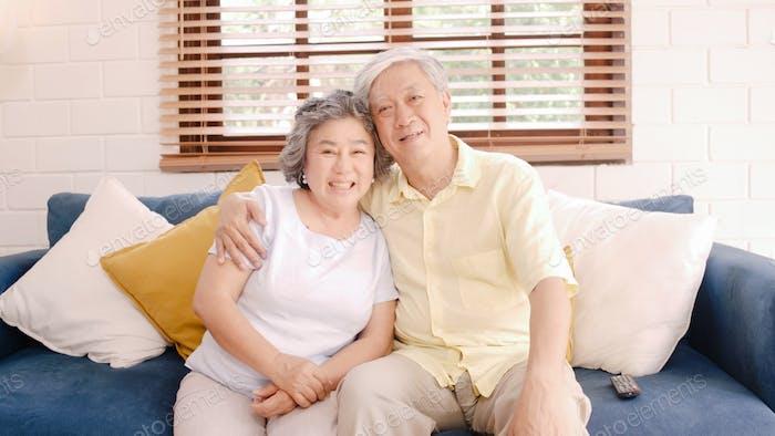 Paar genießt Liebesmoment, während es zu Hause entspannt auf dem Sofa liegt.