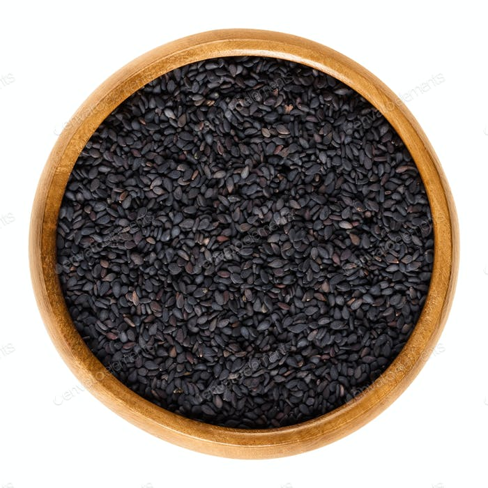 Black sesame seeds, also benniseed, in wooden bowl