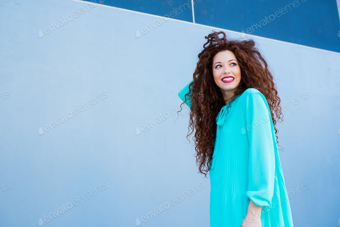 Happy beautiful young redhead woman posing by a colorful wall