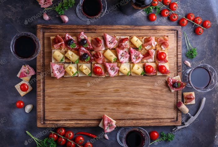 Wooden board with pinxtos or tapas with jamon, ham and sausage, flat lay