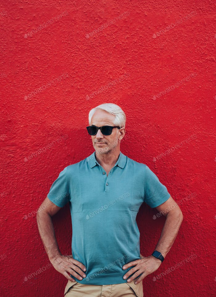 Stylish mature man posing against red wall